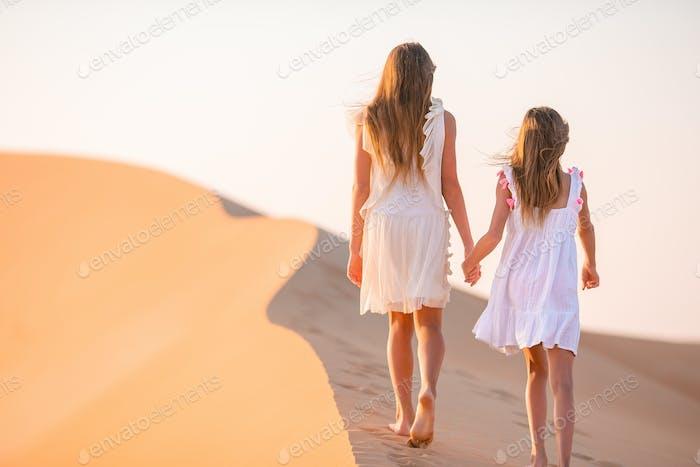 Girls among dunes in Rub al-Khali desert in United Arab Emirates
