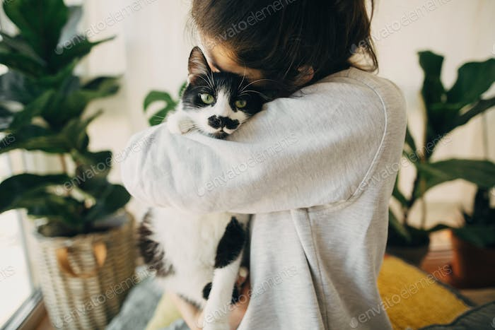 Hipster girl hugging cute cat, sitting together at home