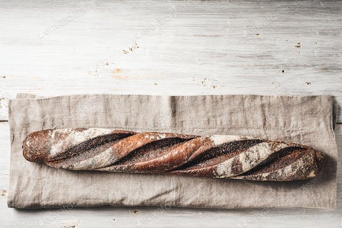 Baguette auf der Serviette auf dem weißen Holztisch horizontal