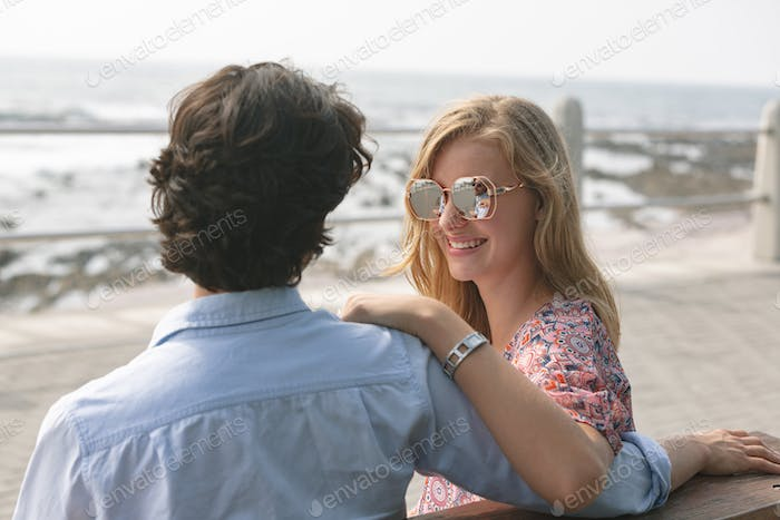 Young couple standing on the promenade with arm around on a sunny day