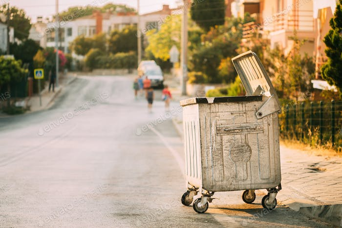 Metal Waste Container On Wheels In Street During Summer Sunny Evening. Container For Temporarily