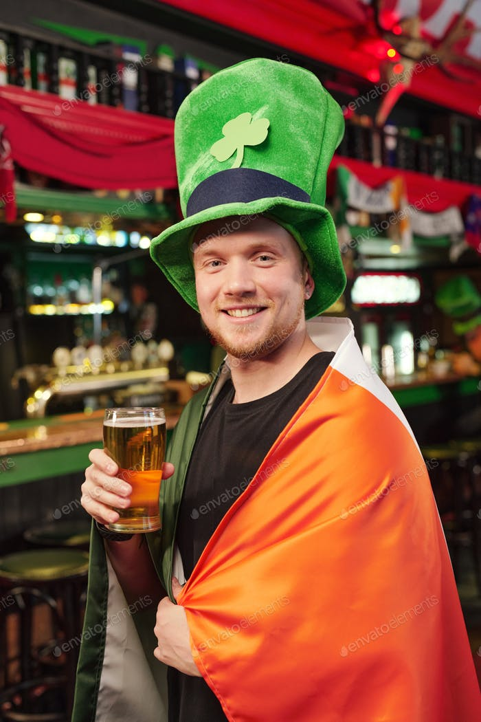 Young cheerful man in green hat looking at you with smile while toasting