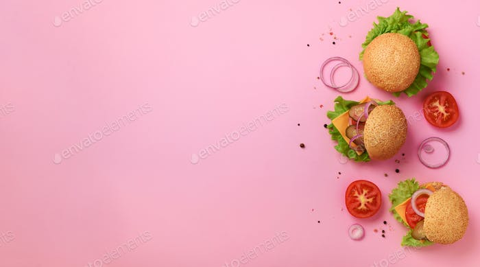 Fast food, unhealthy diet concept. Juicy homemade burgers, tomatoes, cheese, onion, cucumber and