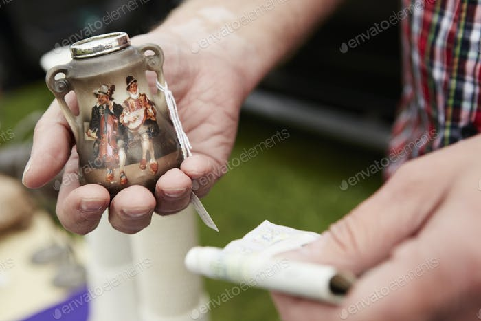 Close up of a man holding a vintage pot and British currency, cash, at a flea market.
