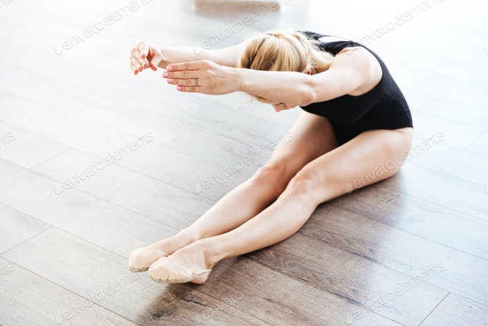 Pretty young woman ballerina sitting and doing stretching exercises