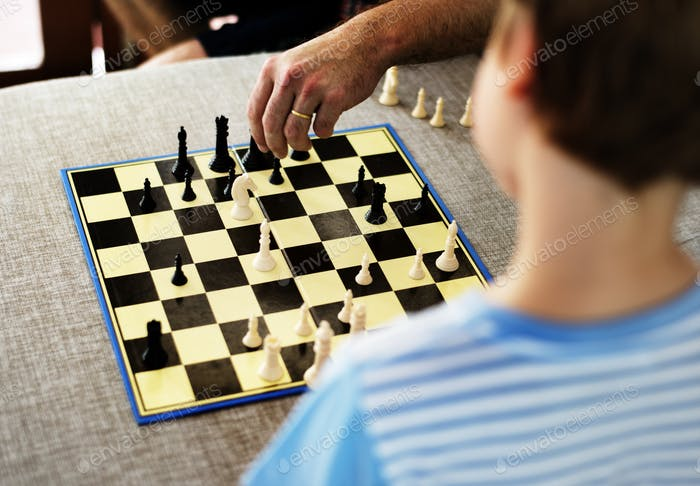 Rear view of young caucasian boy with chess boardgame
