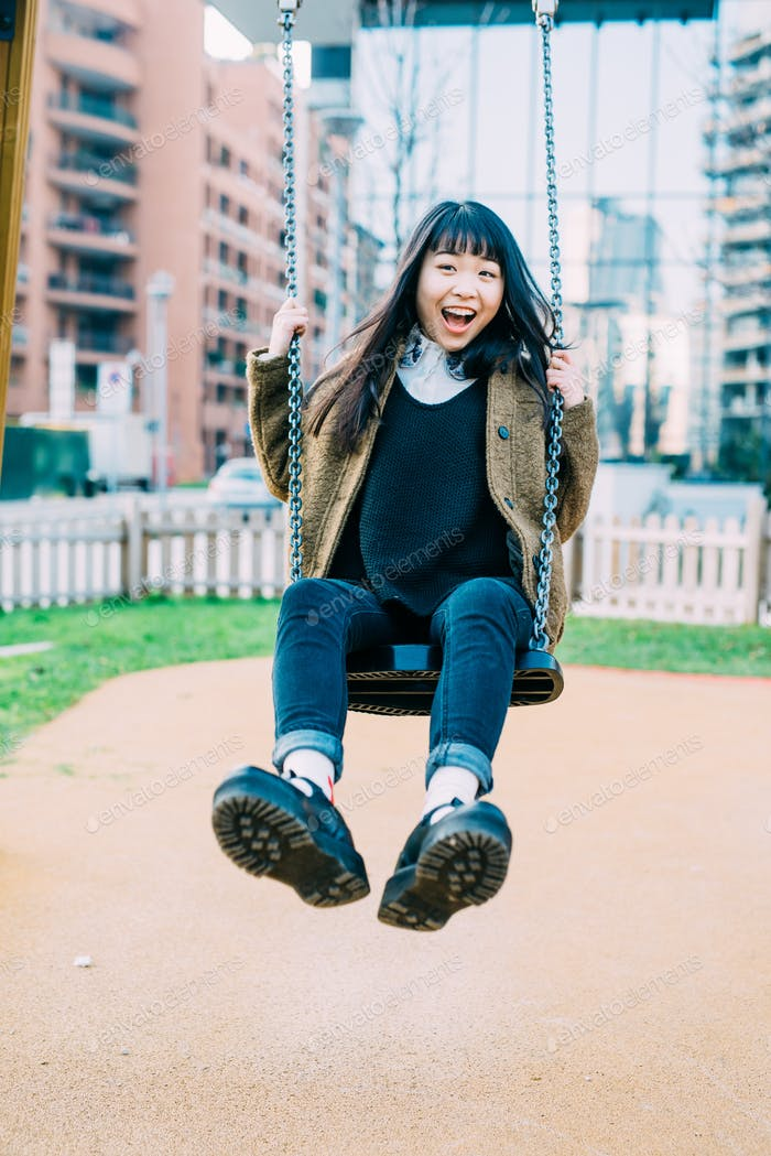 Young beautiful asiatic woman playing on a seesaw in a playgroun