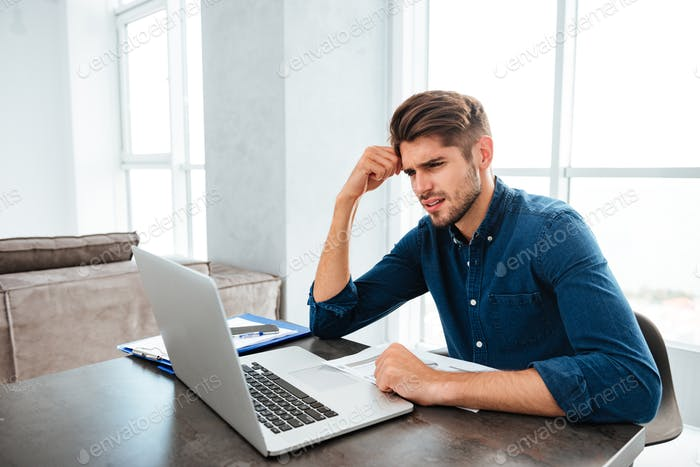Sad young man sitting near laptop and holding head