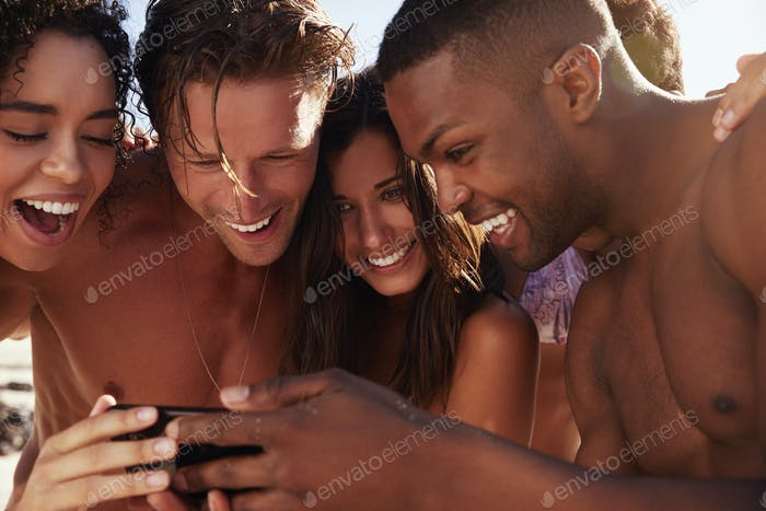 Friends On Beach Vacation Looking At Photo On Mobile Phone