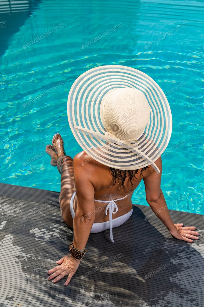 woman at spa resort by the swimming pool.
