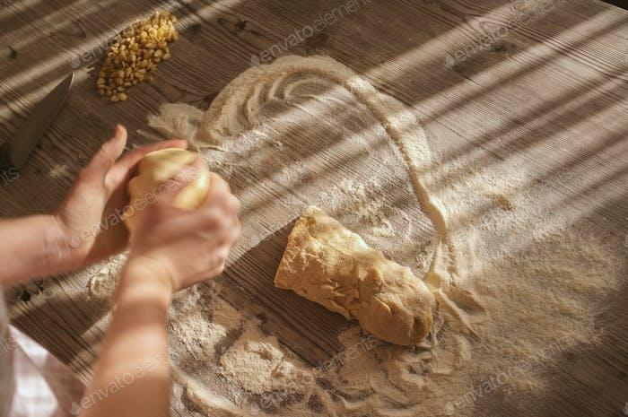 female woman artisan baker at home baking a braided bread (challah)