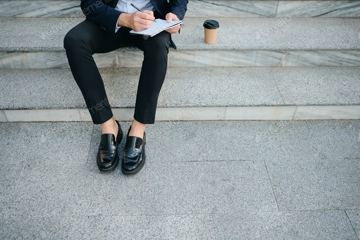 Close up man in classic suit sitting on stairs outdoor writing notes in notepad drinking coffee