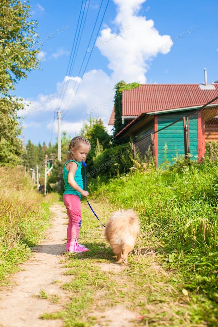 Kleines Mädchen zu Fuß mit ihrem Hund an der Leine