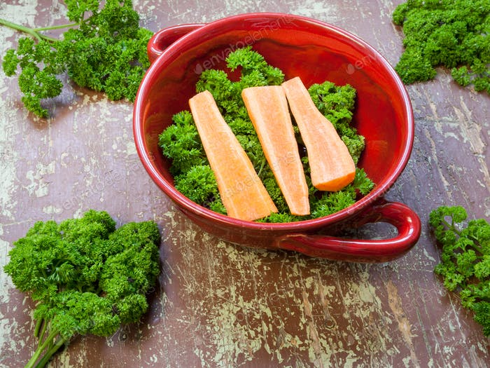 Carrots with green leaves on a wooden background