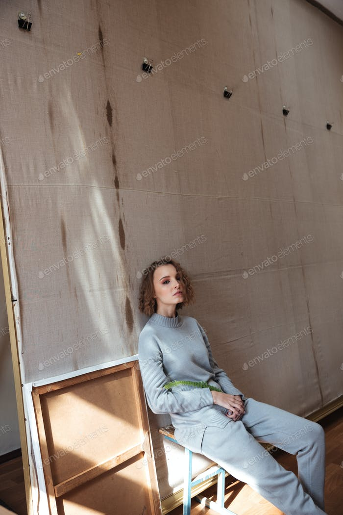 Woman sitting and leaning against a canvas backdrop