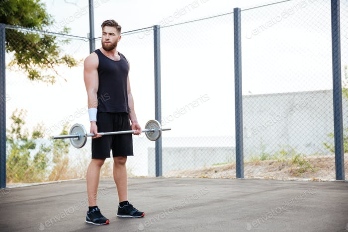 Concentrated young man athlete working out with barbell