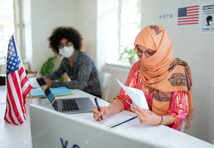 Members of electoral commission in polling place, usa elections and coronavirus
