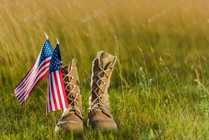 military boots near american flag with stars and stripes on grass
