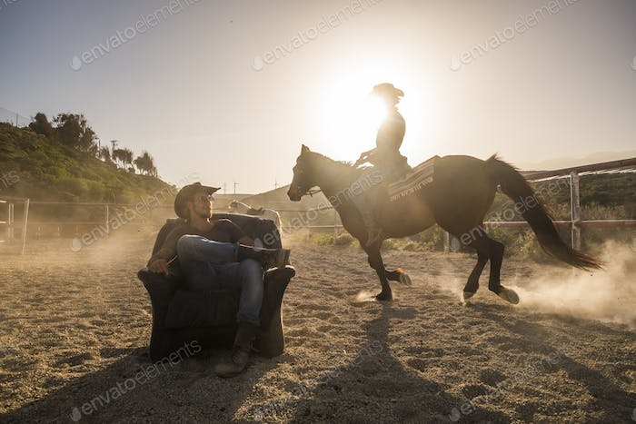 riders with horses in the golden sunset light