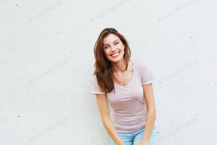 beautiful young lady standing against white wall and smiling
