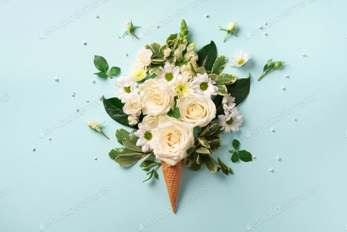 Summer minimal concept. Ice cream cone with white flowers and leaves on blue background. Flat lay