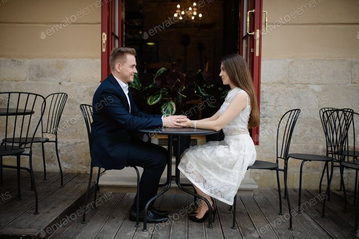 Happy married couple is on a honey moon, having brunch in nice cafe with modern interior
