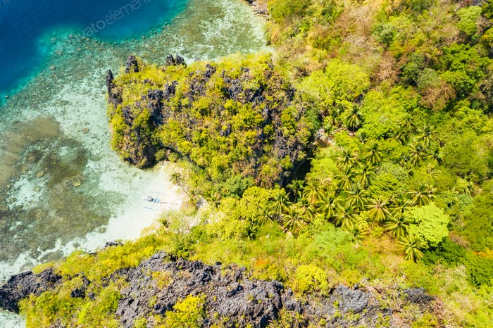 Aerial drone view of secluded beach in jungle with tropical coral reef and small sandy beach