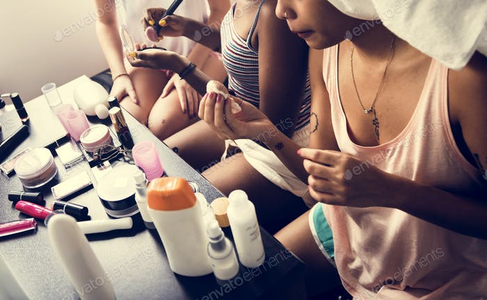 A diverse group of women preparing and using makeups