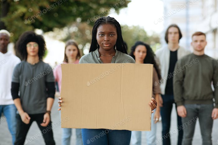Black woman with empty placard leading group of protestors