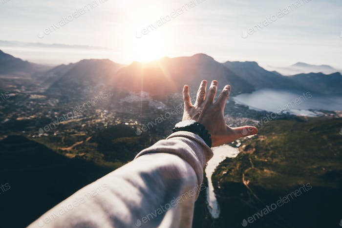 Hand of a man reaching out the beautiful landscape