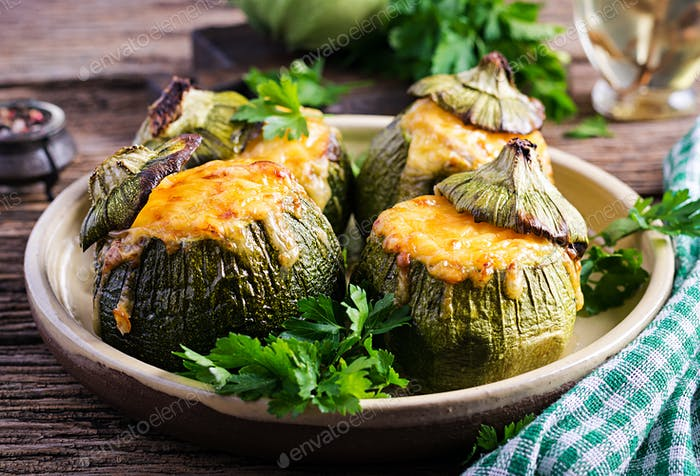 Zucchini stuffed with minced meat, cheese and green herbs. Baked in oven. Top vie