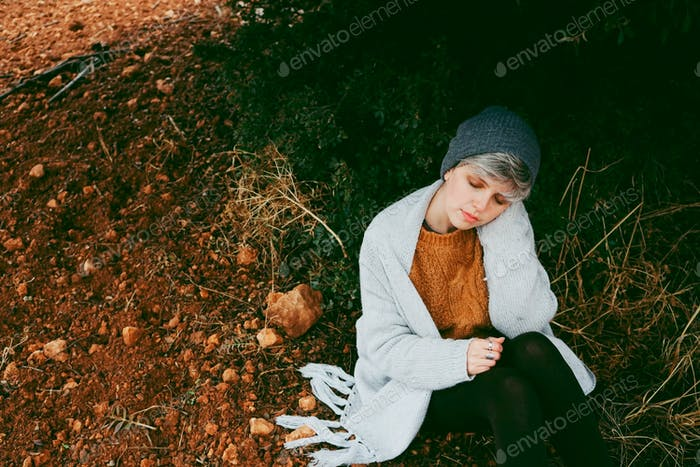 Middle age woman alone in nature in a cold autumn day