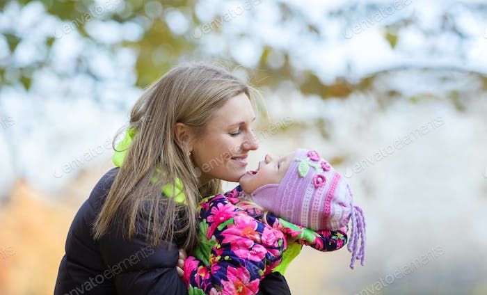 Young mother and daughter having fun outdoors