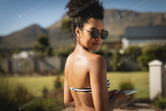 Pretty young woman with sunglasses looking at camera in backyard of her home on a sunny da