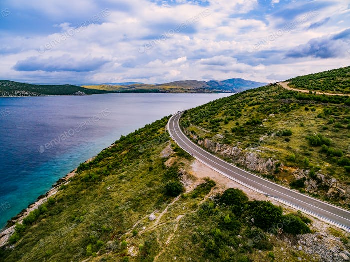 Aerial view of mountain road near the turquoise sea in summer Croatia.