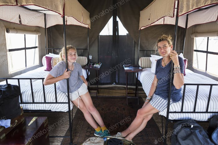 Accomodation at a wildlife reserve camp, a mother and daughter seated on beds in a tent.