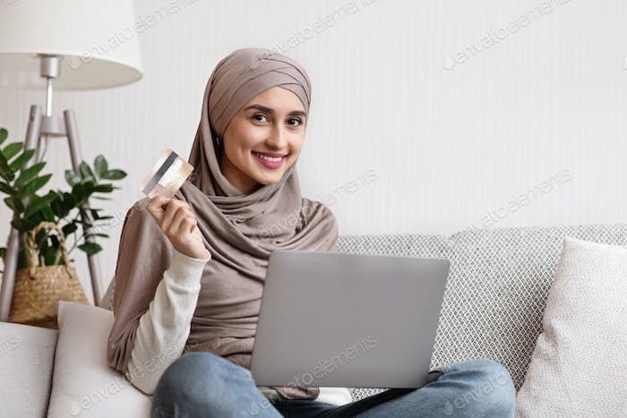 Smiling islamic woman sitting on sofa with laptop and credit card