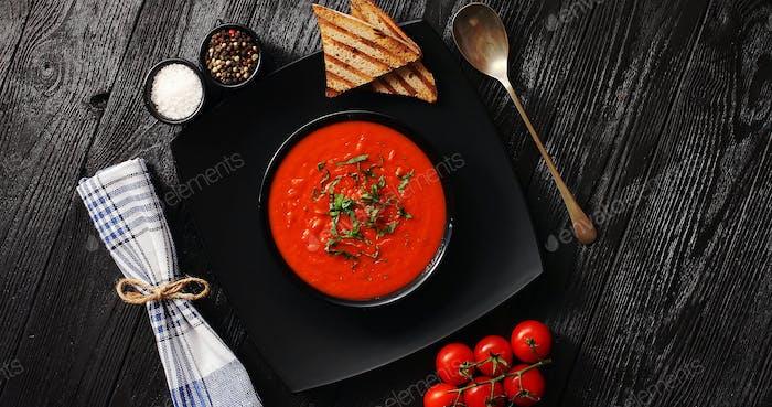 Tomato soup in black bowl with crisp bread