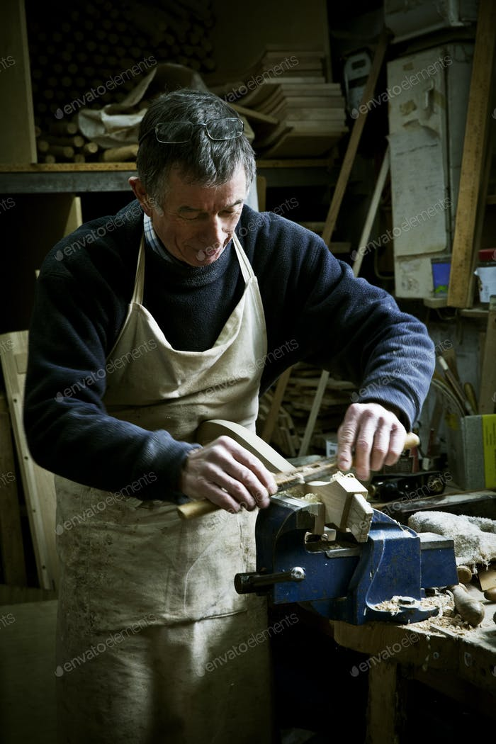 A man working in a furniture maker's workshop, sanding a piece of wood held in a clamp.