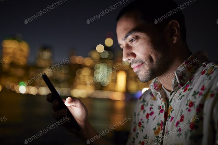 Mann mit Handy in der Nacht mit Stadt Skyline im Hintergrund