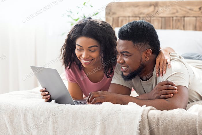 Relaxed african man and woman resting at bedroom, using laptop
