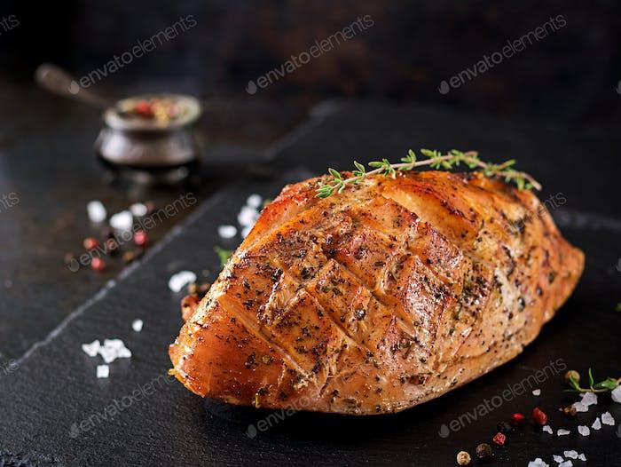 Roasted Christmas ham of turkey on dark rustic background.  Festival food.