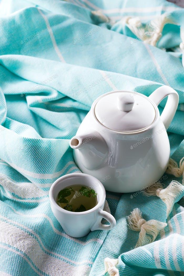Weiße Tasse und Teekanne mit blauem Plaid auf einem Bett. Frühstück im Bett. Süße Heimat