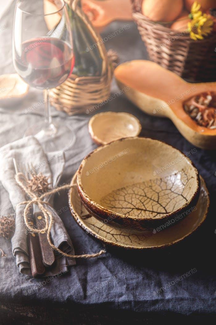 Mesa de otoño con calabazas, cesta y vino tinto. Decoración del Página de inicio de otoño para la cena festiva.