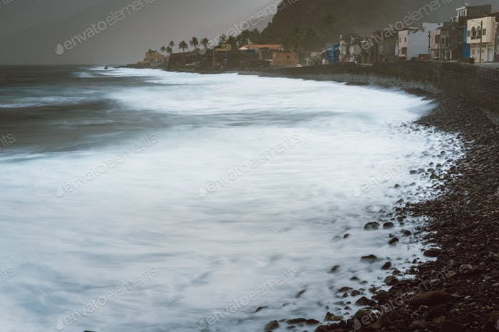Rough ocean waves rolling foamy with blowing spray onto the rocky volcanic shore. Picturesque bay in