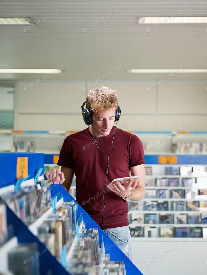 парень слушает музыку в магазине компакт-диск