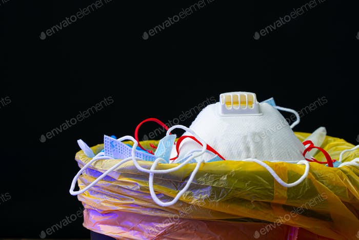 Máscaras infecciosas usadas y guantes médicos en el cubo de basura