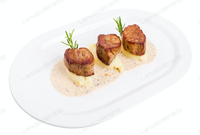 Fried pork tenderloin medallions on mashed potatoes.