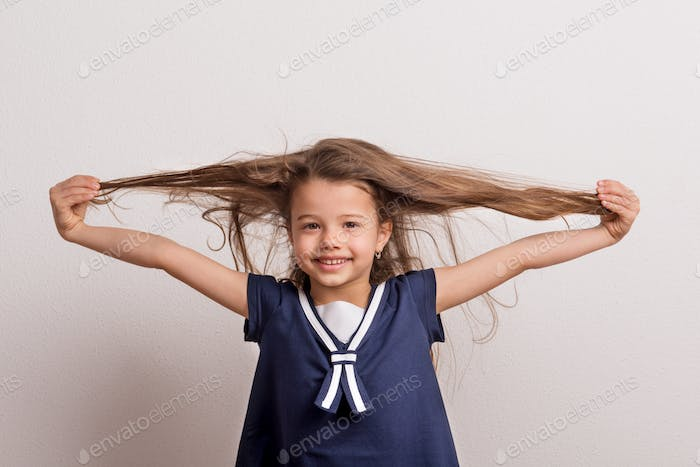 Portrait of a small girl in studio on a white background, holding hair.