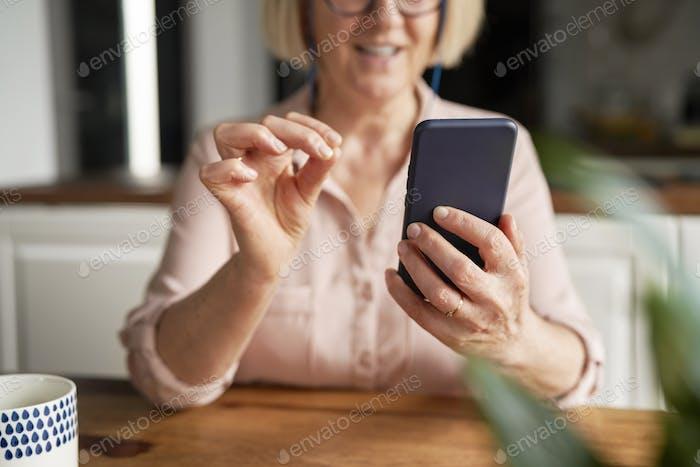 Close up of senior woman using smart phone at home